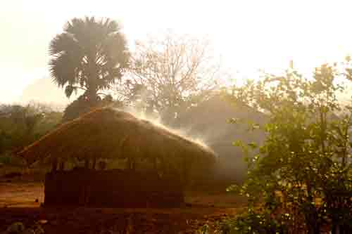 Cooking smoke rising through thatched roof, Mozambique